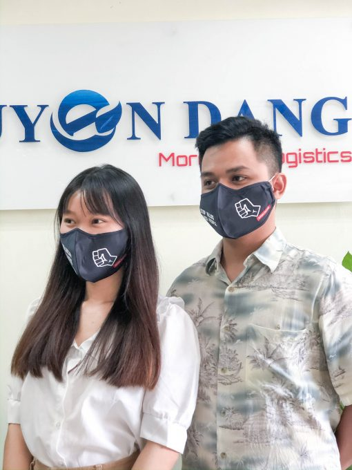couple wears facemask with text